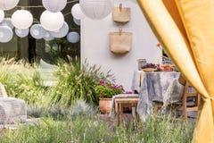 Geel gordijn en witte lantaarns in de tuin met vruchten op lijst, bloemen en zakken Echte foto royalty-vrije stock afbeeldingen