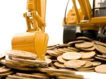 Geel graafwerktuig dat een hoop van muntstukken graaft Royalty-vrije Stock Fotografie