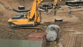 Geel graafwerktuig op een bouwwerf in de zomer stock footage