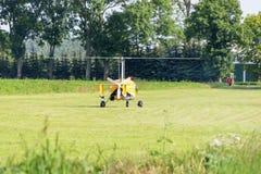 Geel gyrovliegtuig die zich op een weide bevinden stock foto