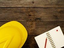Geel helm en potlood op notitieboekje Hoogste mening stock afbeelding