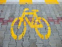 Geel het tekenpictogram van de fietsfiets op de straat de weg openluchtvloer van de asfaltverf grunge Stock Afbeeldingen