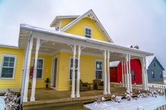 Geel huis met portiek en sneeuwgazon in de winter stock fotografie