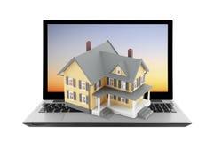 Geel huis op laptop Stock Foto's