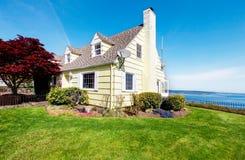 Geel klein huis met watermening en rode esdoorn. stock foto's