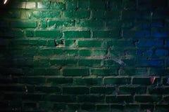 Geel licht van een lantaarn en een blauwe gloed op een bakstenen muur stock foto