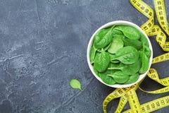 Geel meetlint en groene spinaziebladeren van hierboven Het concept van het dieetvoedsel stock foto