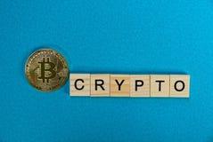 Geel muntstuk bitcoin en woordcrypto van houten brieven op een blauwe achtergrond Royalty-vrije Stock Foto's