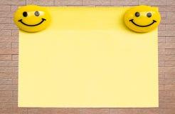 Geel notastootkussen op bakstenen muur Royalty-vrije Stock Foto