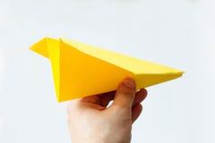 Geel origamivliegtuig op een witte achtergrond Royalty-vrije Stock Afbeelding