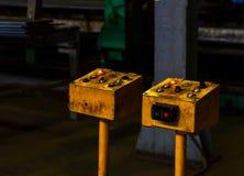 Geel oud uitstekend elektrisch controlebord met knopen om de machines in de workshop voor de productie van zwaar metaalstreptokok stock foto