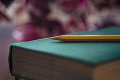 Geel potlood op groen boek Concept onderwijs Close-up met gradi?ntachtergrond met reverberatie Selectieve nadruk stock afbeelding