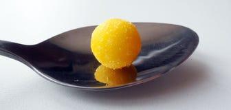 Geel rond suikergoed op een close-up van de ijzerlepel vector illustratie