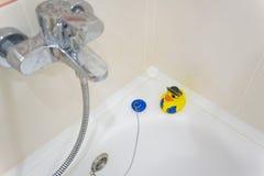 Geel rubber duckie op rand van badkuip Stock Foto