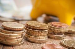 Geel spaarvarken op euro muntstukken en bankbiljetten op wo Stock Foto's