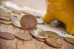 Geel spaarvarken op euro muntstukken en bankbiljetten op wo Royalty-vrije Stock Afbeeldingen