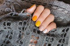 Geel spijkerontwerp Mooie vrouwelijke hand met manicure met verschillende schaduwen van geel Stock Afbeelding