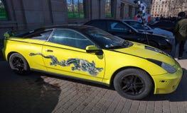 Geel sportief gestileerd Toyota Celica met draak het schilderen Stock Afbeelding