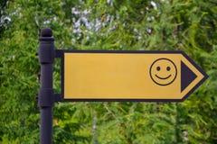 Geel teken met een glimlach op de straat De pijl toont Model stock foto