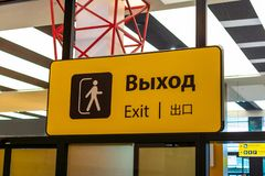 Geel teken met een zwarte inschrijvingsuitgang in verschillende talen bij de luchthaven royalty-vrije stock foto