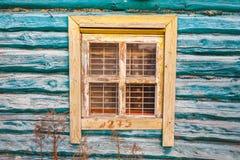 Geel venster in oud turkoois blokhuis stock fotografie