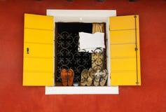 Geel venster, rode muur, schoenen op de vensterbank Royalty-vrije Stock Afbeeldingen