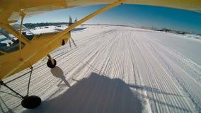 Geel vliegtuig die op sneeuw landen stock videobeelden