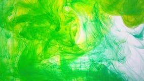 Geelgroene verf die in water wervelen Zachte beweging van de inkt in het water stock videobeelden