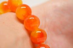 Geeloranje armbandparels op pols Royalty-vrije Stock Fotografie