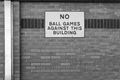 Geen die teken van het Balspelmetaal op een schoolbakstenen muur wordt gezien stock fotografie