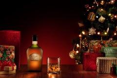 GEEN EMBLEEM OF HANDELSMERK! ZELF GEMAAKTE ETIKETTEN! sluit omhoog mening van fles en glas met rum op kleurenrug stock foto