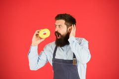 Geen manier Ware feiten over suiker Verglaasde doughnut van de Hipster de gebaarde bakker greep op rode achtergrond Koffie en bak royalty-vrije stock fotografie