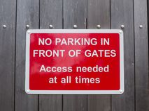 Geen parkeren voor poortentoegang vergde op elk moment rood park stock fotografie