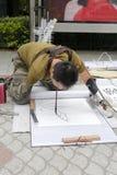 Geen wapenmens die op de grond, het bijten borstel liggen die het Chinese schilderen trekken Stock Foto