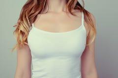 Geerntet nah herauf Foto von Frau ` s Brust im weißen T-Shirt; sie h lizenzfreie stockfotos