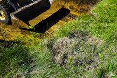 Geerntete Ansicht des Planierraupeneimers an den Aushubarbeiten auf grasartigem Sektor lizenzfreie stockfotos