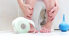 Geerntete Beine einer Frau, sitzend auf einer Toilette mit gesenktem Schlüpfer, blauem Reinigungsklistier und einer Rolle des Toi stockbild