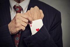 Geerntete Bildmannhand, die ein verstecktes As vom Ärmel auszieht Lizenzfreies Stockbild