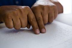 Geerntete Finger auf dem älteren Mann, der Blindenschrift liest, reservieren bei Tisch Stockfotografie