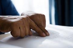 Geerntete Hände auf dem älteren Mann, der Blindenschrift liest, buchen im Ruhesitz Stockbilder