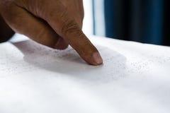 Geerntete Hände auf dem Mann, der Blindenschrift liest, buchen im Ruhesitz Stockfoto