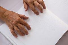 Geerntete Hände der älteren Frau Blindenschrift im Pflegeheim lesend Stockfoto
