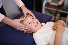 Geerntete Hände des weiblichen Therapeuten Kopfmassage gebend dem Jungen, der auf Bett liegt Stockfotografie