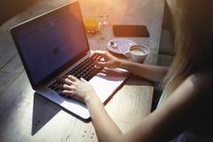 Geerntete Schussansicht von Frauenfreiberufler Keyboarding auf Laptop-Computer mit Kopienraumschirm beim Sitzen im Café Lizenzfreies Stockfoto