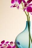 Geernteter blauer Vase mit rosafarbenen Orchideen stockfotos