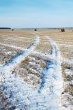Geernteter Schnee bedeckte Ackerland mit Rollen des gemähten Strohs Stockbilder