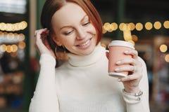 Geernteter Schuss der angenehmen schauenden Frau wirft Café im im Freien, hält den Papiertasse kaffee auf, gekleidet in der weiße stockfoto