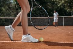 geernteter Schuss der Frau mit dem Schläger, der über dem Tennisballlügen steht lizenzfreie stockfotos