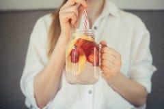Geernteter Schuss der jungen Frau nach Hause gemachtes frisches Sommer drin trinkend stockfotos