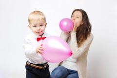 Geernteter Schuss der Mutter und ihr Sohn, der mit roten Ballonen spielt Stockfotografie